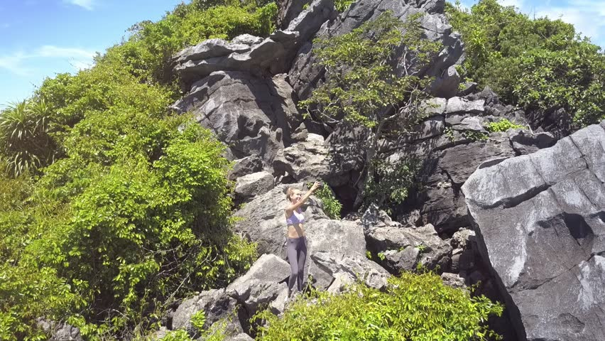 Drone removes from brave blond girl making selfie on steep mountain top covered with tropical plants