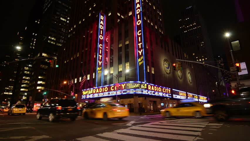 NEW YORK, NEW YORK, April 6th 2017: A 3 clip montage of the exterior of Radio City Music Hall on 6th Avenue in Manhattan, New York. Vehicles can be seen driving past as well as pedestrians walking.