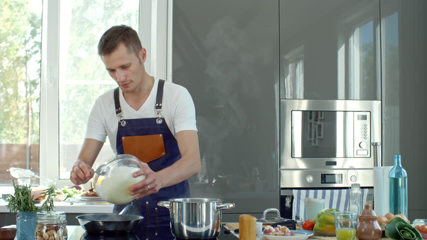 Medium shot of cooking show presenter in apron standing at kitchen countertop and adding cream sauce into hot pan, then stirring with spoon while explaining recipe before camera