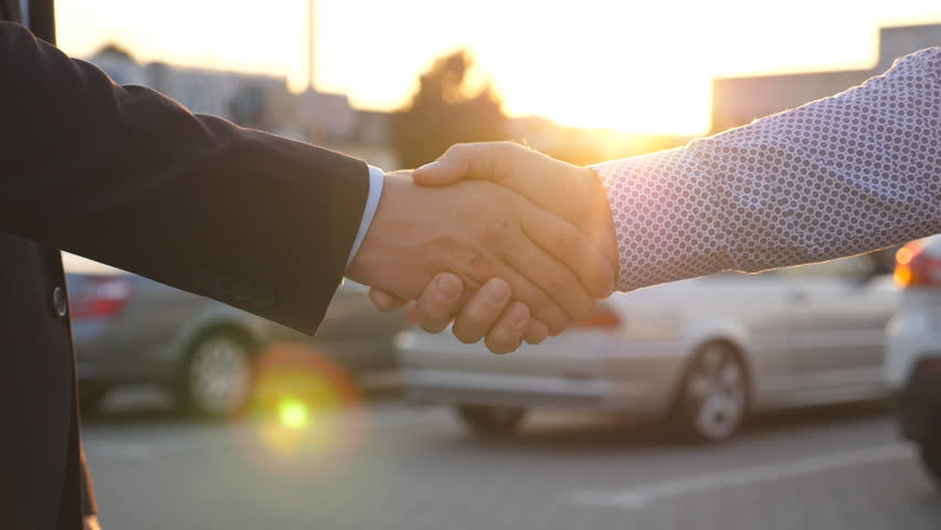 Two businessmen shaking hands of each other with cars in parking at background. Handshake between manager or dealer and client. Shaking of male arms outside. Close up Slow motion