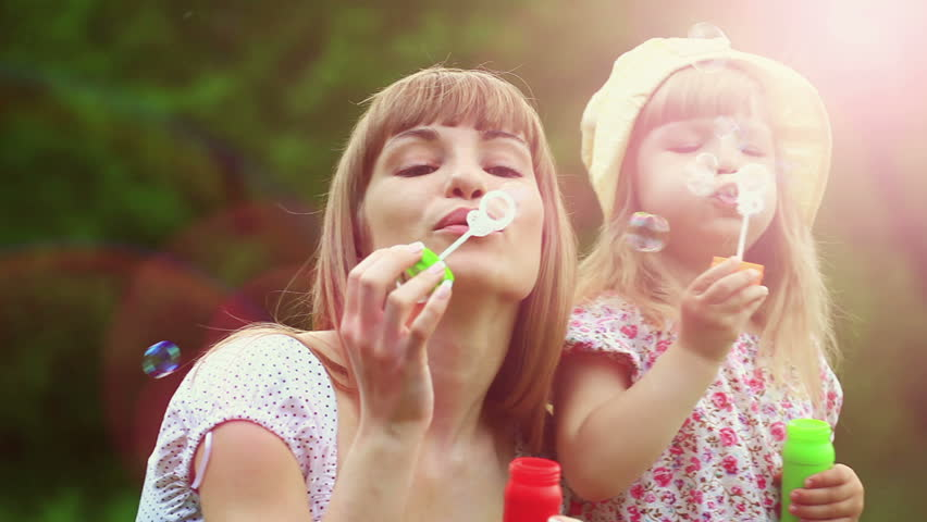 Sunny family blowing air bubbles. Lens flares | Shutterstock HD Video #3365021