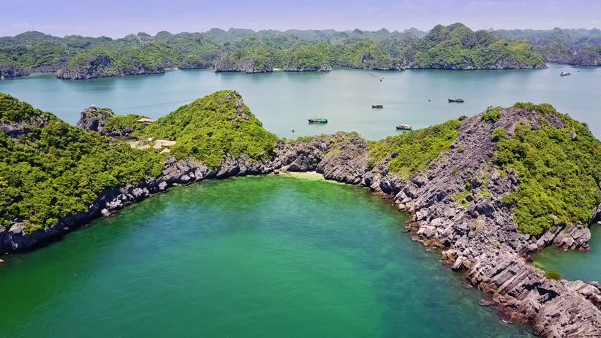 drone motion over pictorial azure bay with large and small cliff islands of whimsical shape in famous park Ha Long