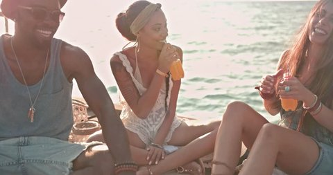 Happy multi-ethnic hipster friends on summer holidays having fun and drinking orange soda on jetty