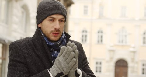 Portrait shot of the handsome man in a hat and gloves standing on the street in winter time and warming his hands and shoulders. cold day. Town architecture on the background. Outdoors
