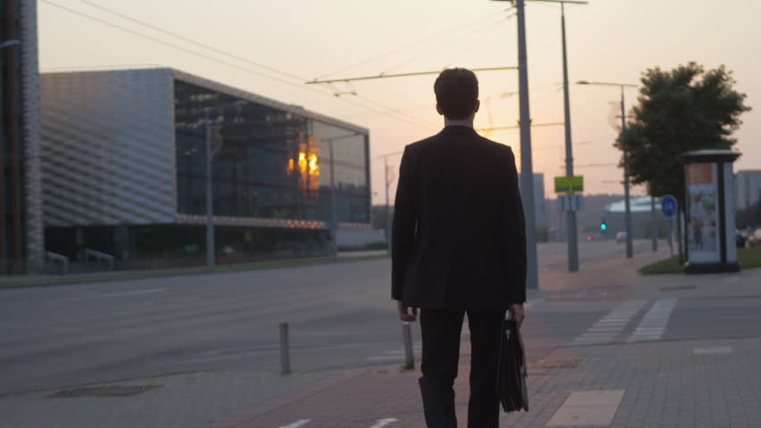 Successful young man walking on the street in the city. Businessman wearing a suit and holding a briefcase ready for a brand new day early in the morning. | Shutterstock HD Video #33670408