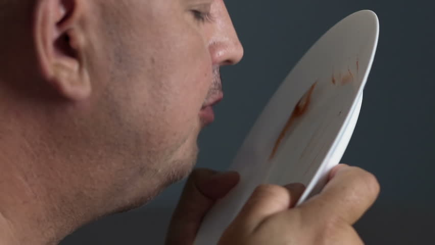 Obese guy eating remains of ketchup and mayo from plate, junk and greasy food