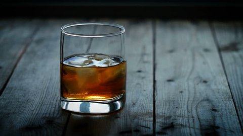 Glass with ice and scotch whiskey on wooden glass