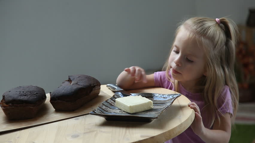 Little child eating butter with her finger. Adorable girl with long blond hair stealing butter from plate | Shutterstock HD Video #33677731