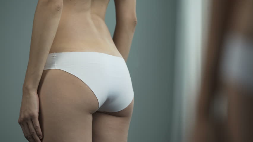 Woman in white panties posing in front of mirror, anti-cellulite cosmetics