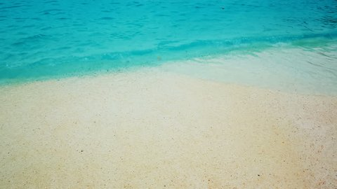 Inspirational beautiful slow motion turquoise waters lapping the pristine sands of Marble Beach in Greece, also known as Saliara. The beach has pearl-like white pebbles and deep blue waters