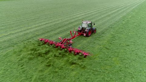 Aerial bird-eye view showing tractor raking grass mixing the grass for drying so it can be baled picked up and it will be used as cattle fodder in winter time beautiful fresh green grass field 4k