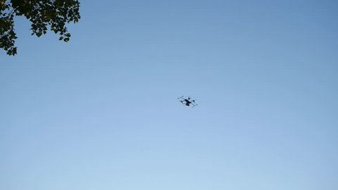 A self build drone flies through the sky in a field in summer