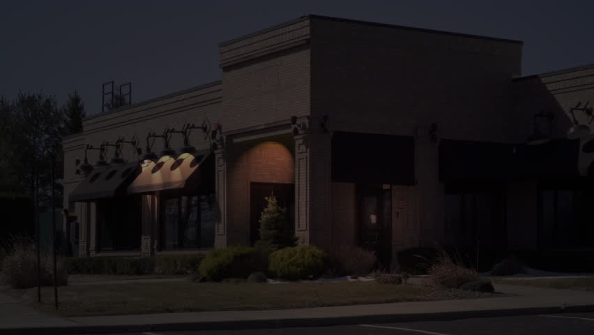 NX restaurant exterior establishing shot night time. Outside of generic family stand alone eatery building on dark evening. No people or signage. Matching Day / night video available
