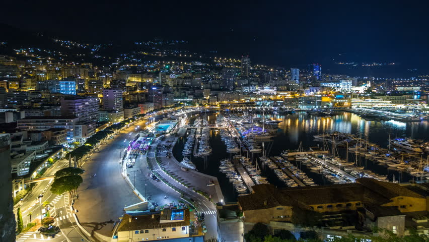 Panorama of Monte Carlo timelapse hyperlapse at night from the observation deck in the village of Monaco with Port Hercules. Buildings with illumination and yachts in harbor aerial top view. Traffic