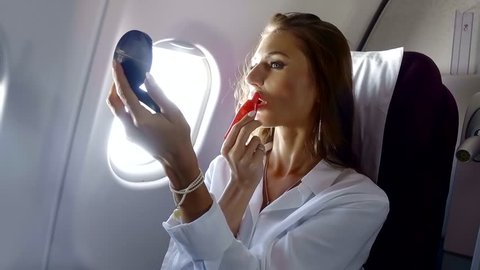 attractive businesswoman is applying lip balm on her lips and looking in a small mirror, sitting in a modern airplane
