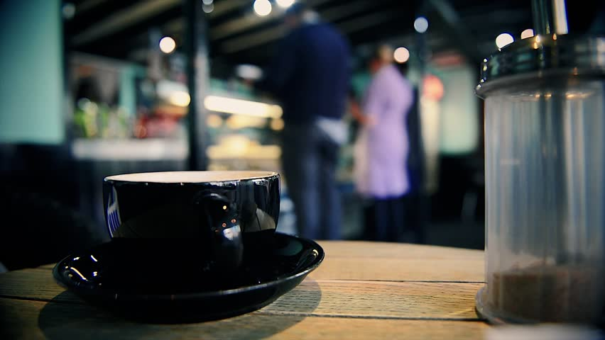 Close-up shot of a cappuccino cup in an urban coffee shop.