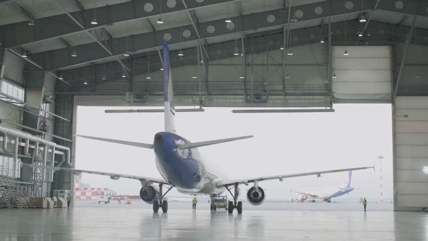 Passenger plane maintenance engines and fuselage repair leaves the hangar of the airport. Airbus for maintenance in the hangar, rear view. Plane leaves the hangar after repairs