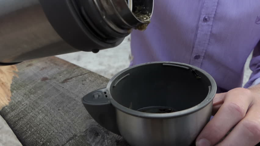 Young man pours green tea from a flask in his cup in slo-mo | Shutterstock HD Video #33773251