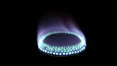 Natural gas inflammation in stove burner, close up view, Gas-stove on the black background, gas burning from a kitchen gas stove in slow motion. Stove top burner igniting into a blue cooking flame.