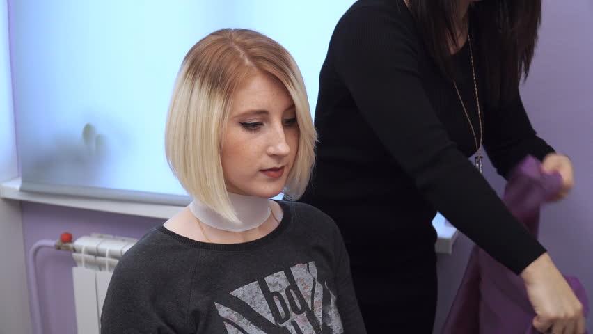Preparing a blonde for a haircut. Woman getting new haircut by hairdresser at beauty salon. polishing hair | Shutterstock HD Video #33820591