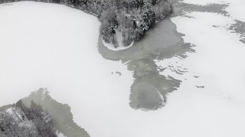 flight over the snow forest and the frozen lake into the fog and over the clouds.Snow-covered tree crowns, in the first snow before the new year.
