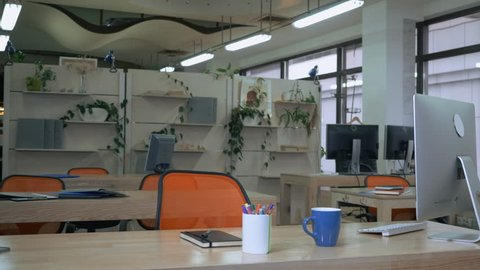 empty office without employees. room with working place and orange chairs computers on wooden desk