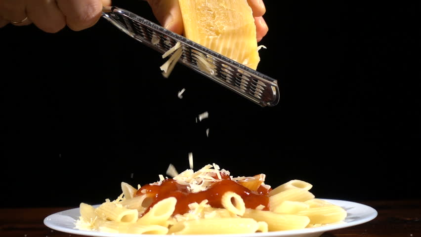 adding a cheese that rubbing to pasta in plate with metal grater, slow motion