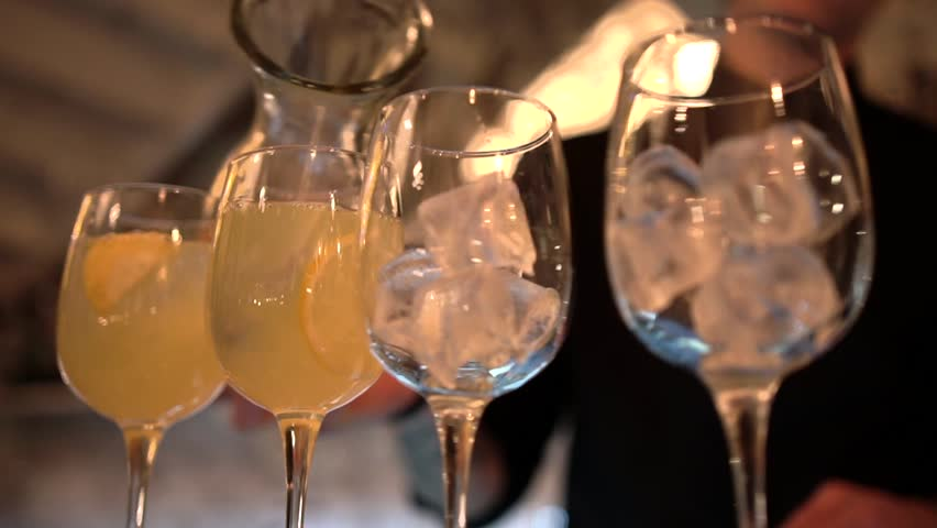 Bartender silhouette fills a set of transparent glass goblets with ice cubes and lemonade on a bar background, close-up.