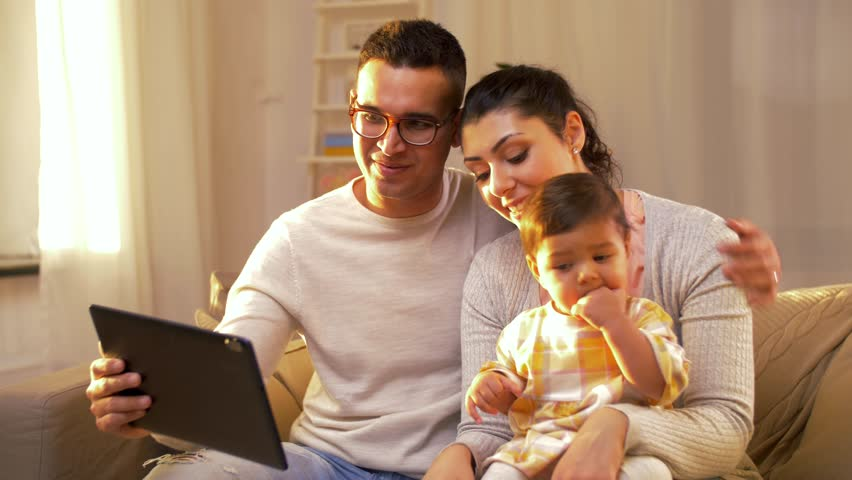 Family, parenthood and people concept - happy mother, father and baby with tablet pc computer having video call at home | Shutterstock HD Video #33843601