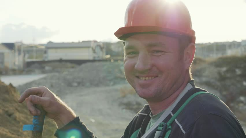 Against the sun portrait of construction worker in helmet with shovel standing near the sand pile. Builder looking at camera and smiling at construction site, slow motion.