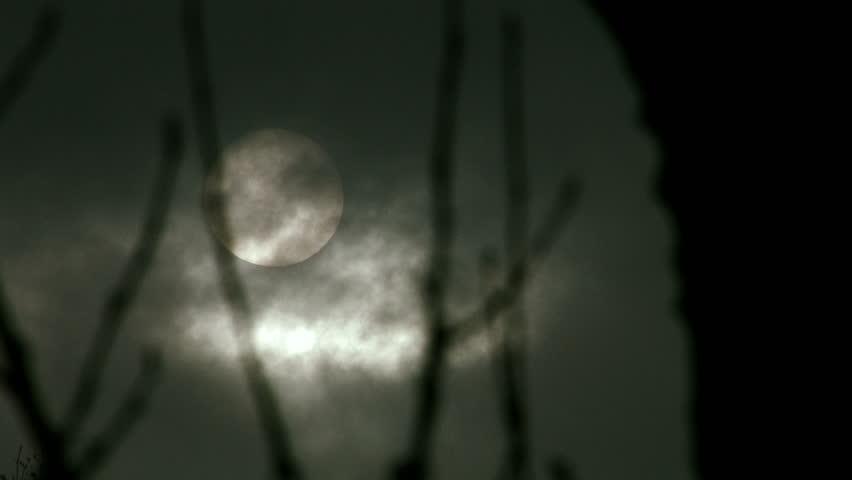 Still shot of the winter sun peeking through dark clouds.