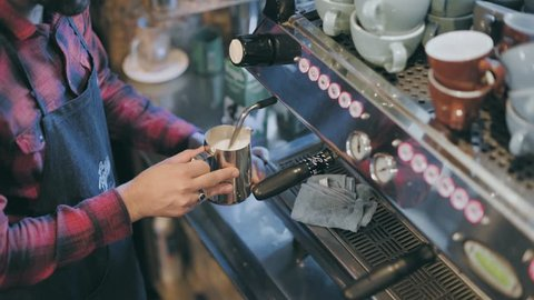 Overhead shot of barista at downtown trendy specialty coffee place, steams milk in jug, creates latte art in small cup with espresso shot. Artisan authentic business owner