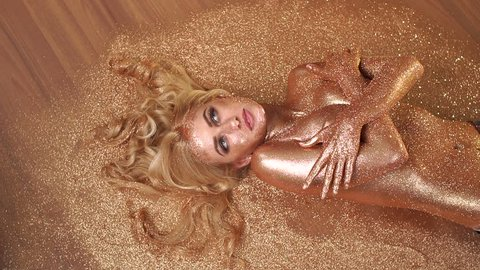 Beautiful model with Golden skin and blonde long hair lying naked on the floor on gold glittery dust. Slow motion. Golden make-up.