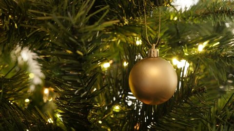 Matte gold color bauble hanged on the artificial tree 4K 2160p 30fps UltraHD footage - Golden Christmas ornament with fairy lights close-up 3840X2160 UHD video