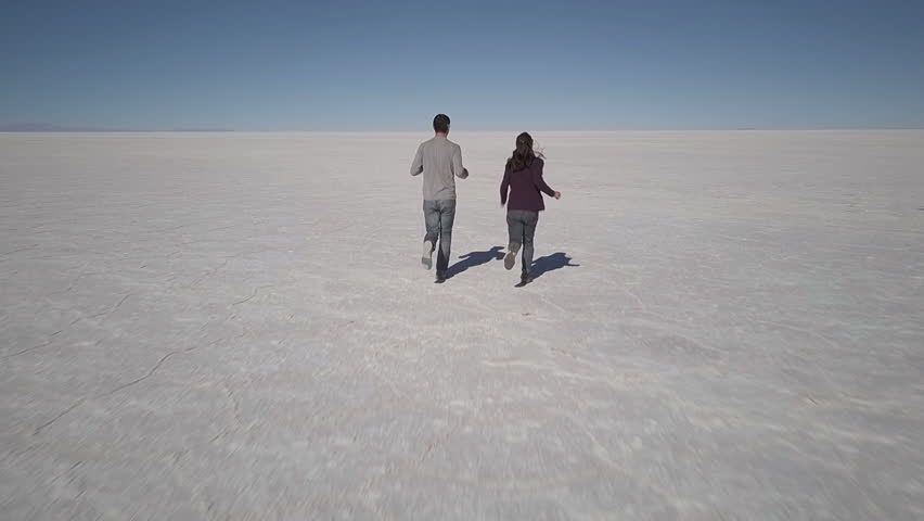 2 people run in slow motion on the salt flats in the Salar de Uyuni