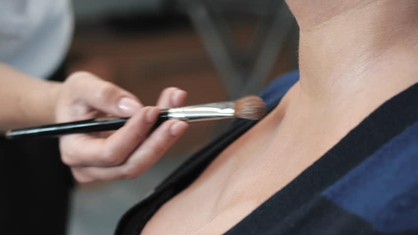 Professional makeup artist applying powder on model's decollete area. Beauty salon. Slow motion.