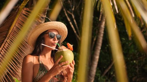 Young Attractive Mixed Race Tourist Girl Drinking Fresh Thai Coconut Water at Tropical Beach. 4K, Slowmotion. Phuket, Thailand.