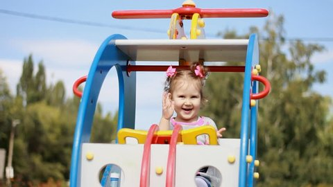 A little sweet girl is riding a carousel helicopter in an amusement park. A child plays in the playground. Entertainment for children.