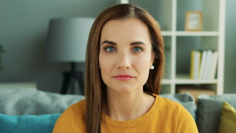 Close up of charming woman face with a nice smile on the living room background. Portrait. Zoom in and zoom out. Indoor