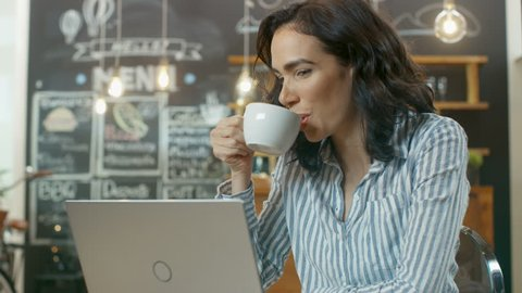 Beautiful Woman Works on a Laptop while Sitting in Cafe. Other Customer and Waiter Walking in the Background of This Stylish Coffee Shop. Shot on RED EPIC-W 8K Helium Cinema Camera.