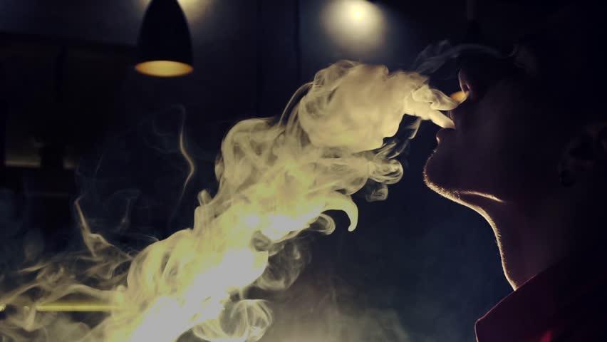 Young man smoking hookah in a bar