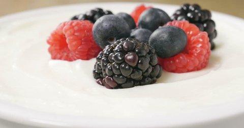 Composition of a typical genuine breakfast made with yogurt, blueberries, raspberries, blackberries, muesli. Concept of: fitness, diet, wellness and breakfasts.