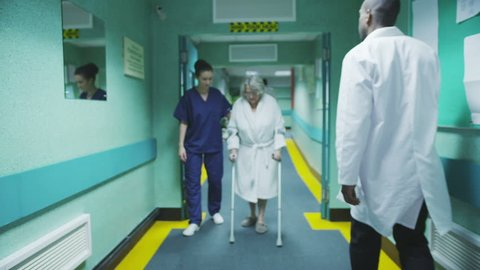 An attractive female medical assistant or nurse helps an elderly lady on crutches to take a walk down the hospital corridor. In slow motion.