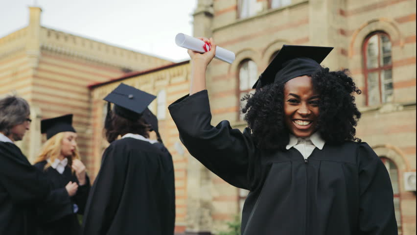 Portrait of the African American happy young graduated woman posing to the camera, showing her diploma and making YES gesture in front of the University. Graduates with professor on the background