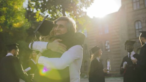Rear of the blonde female graduate being congratulating with graduation by her gray-haired father on a sunny day. Outside