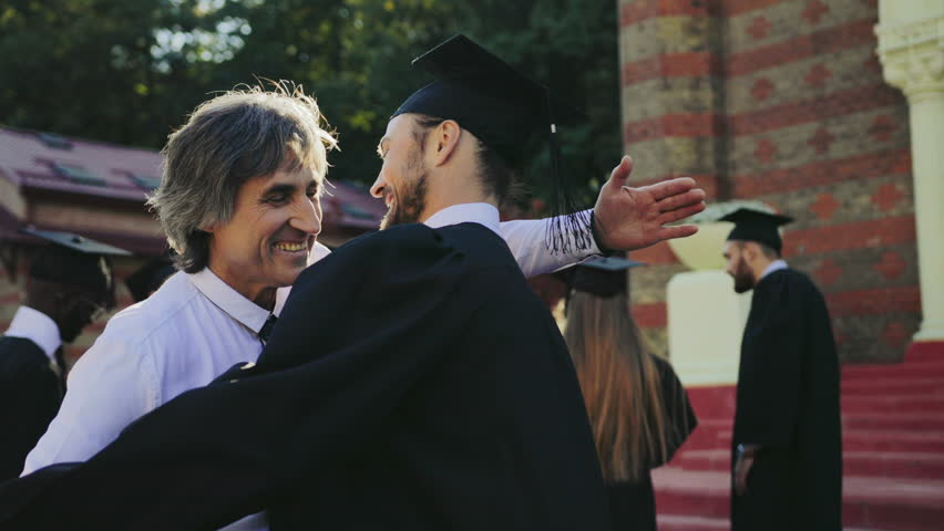 Handsome male graduate hugging with his father, dad congratulating his son with a graduation from University. Outdoor