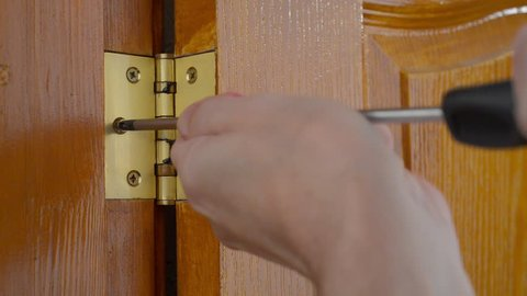 A man is using a screwdriver to screw a Door hinge