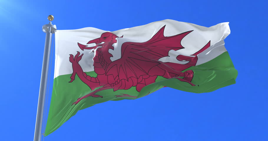 Flag of Wales waving at wind in slow with blue sky, loop