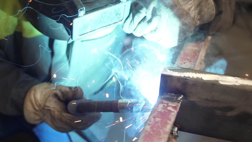 worker welding steel with mig welder machine slow motion
