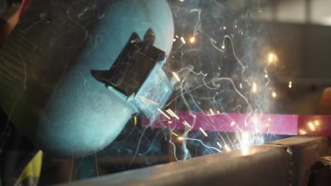 worker welding steel with mig welder machine slow motion